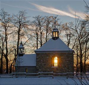 A lit church in the snowy dusk.