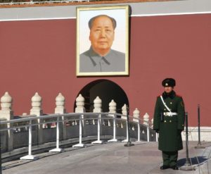 A Chinese soldier standing in front of a picture of Chairman Mao.