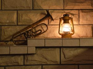An old trumpet and a lit lantern on the shelf of a stone wall.