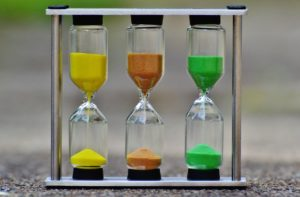 A set of three hourglasses, with yellow, rust and green sand flowing.