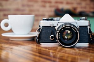 A real SLR camera on a wood table, next to a white coffee cup.