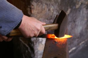 A blacksmith shaping a spear point on an anvil.