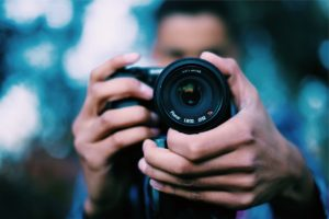 close-up of a photographer's hands adjusting a lens while taking an image.