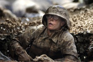 Muddy female soldier in a foxhole.