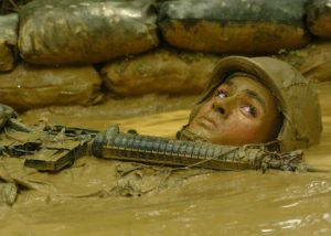 A armed soldier in a foxhole with his body almost completely submerged in mud.