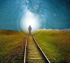 A man walking at night on some railroad tracks toward a bright circular light.