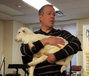 An image of my pastor holding a living lamb in his arms a week before Easter Sunday.
