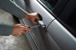 A pair of hands try to break into a car.
