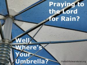 Underneath a blue and white umbrella, sprinkled with raindrops.