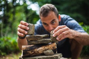 A man carefully stacking a pile of rocks in the wilderness.