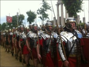 Men dressed up and marching as soldiers in a Roman legion.