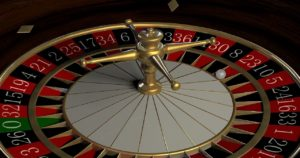 A roulette gambling wheel with the white ball on red 23.