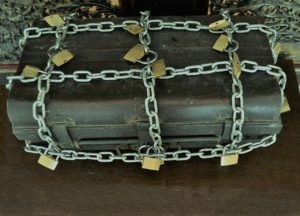 A strongbox completely chained and padlocked.