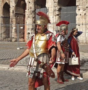 Two Roman legionnaires and a woman dressed in ancient clothes.